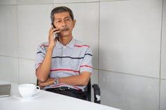 Den pensionärAsien affärsmannen sitter och osemobiltelefonen royaltyfria bilder