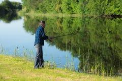 Den pensionerade aktiva mannen fiskar på flodbanken Arkivfoton