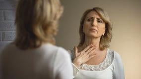 Den pensionerade kvinnan som ser SAD in i spegeln, utseendemässigt problem för ålder, rynkar arkivfilmer