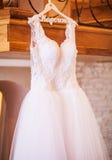 Den perfekta bröllopsklänningen med en full kjol på en hängare i ret Royaltyfri Foto