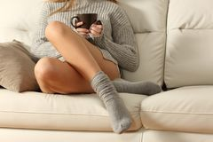 Den perfekta kvinnan vaxade ben på en soffa i vinter royaltyfri fotografi