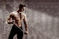 Den perfekta manliga kroppen - enormt posera för kroppsbyggare Rym en kedja med tatueringen Arkivfoto