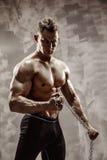 Den perfekta manliga kroppen - enormt posera för kroppsbyggare Rym en kedja med tatueringen Arkivfoton