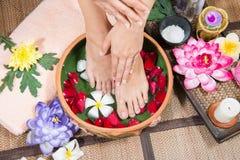 Den perfekta rena asiatiska kvinnliga härlig och elegant ansade för flicka` s handen för fot, trycker på hennes fot, Spa, skurar  Arkivfoton