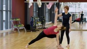 Den personliga instruktören på idrottshallen hjälper en kvinna att göra en yogaövning stock video