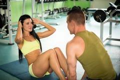 Den personliga konditionlagledaren utbildar den härliga kvinnan i idrottshall Royaltyfri Bild