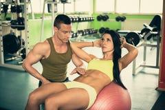 Den personliga konditionlagledaren utbildar den härliga kvinnan i idrottshall Royaltyfria Foton