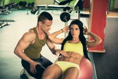 Den personliga konditionlagledaren utbildar den härliga kvinnan i idrottshall Arkivbild