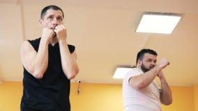 Den personliga lagledaren ger individuell boxas utbildning till en fyllig man i idrottshall Övningar som förlorar vikt för tjock  arkivfilmer