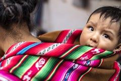 Den peruanska infödda modern bär henne för att behandla som ett barn sonen på hennes baksida royaltyfri foto