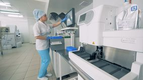 Den Pharmacutical laboratoriumarbetaren skriver på en bildskärm av en maskin som utför provet av blodprövkopior lager videofilmer
