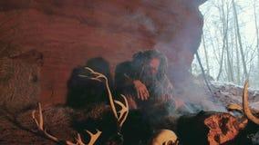 Den Phehistoric mannen röker cigaretten i hans grotta på en bakgrund av den snöig skogen arkivfilmer