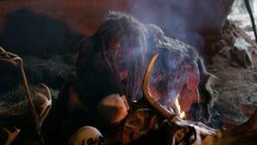 Den Phrehistoric grottamannen gör första brand, slag på den i hans grotta på bakgrunden av ben och skallar Snövinter lager videofilmer