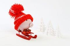 Den Piggy asken med den röda hatten med pompomanseende på röda släde- och för innehav tre gåvor med den guld- pilbågen på snö och Royaltyfri Foto