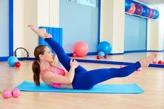 Den Pilates kvinnan scissor övningsgenomkörare på idrottshallen Royaltyfri Bild