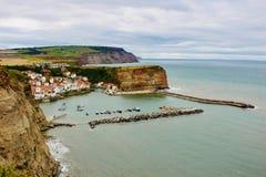 Den pittoreska hamnen och den gamla byn av Staithes kura ihop sig i klippor royaltyfria foton