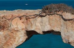 Den pittoreska sikten av ett naturligt vaggar bron på havet Arkivfoto