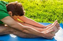 Den placerade framåt krökningen poserar Övande Yoga Royaltyfri Bild