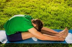 Den placerade framåt krökningen poserar Övande Yoga Fotografering för Bildbyråer