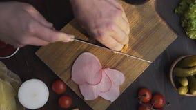 Den plana lekmanna- videoen av smaklig naturlig skinka skivas av den skarpa kniven på träbrädet, knyckigt rökt kött som gör av lager videofilmer