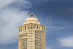 Den plana Qatar Airways flyger över moderna byggnader Royaltyfria Foton
