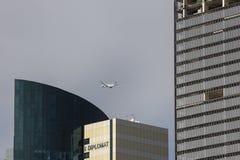 Den plana Qatar Airways flyger över moderna byggnader Royaltyfri Fotografi