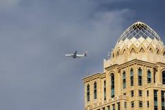 Den plana Qatar Airways flyger över moderna byggnader Royaltyfri Bild