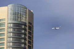 Den plana Qatar Airways flyger över moderna byggnader Royaltyfria Bilder