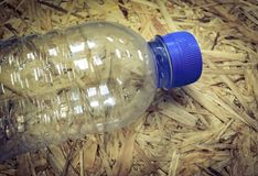 den plast- flaskan på gammal wood bakgrund, tappning och retro färg tonar Royaltyfria Bilder