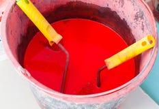 Den plast- hinken med röd målarfärg, innan de målar och målarfärgrullar med gula handtag är i lägenhet under under-renovering Arkivbilder