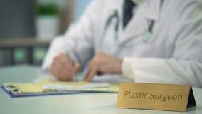 Den plast- kirurgen som avslutar medicinsk dokumentation som är fyllnads- bildar ut, i klinik stock video