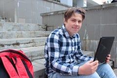 Den pojketonåringskolpojken eller studenten sitter på trappan och att arbeta i datoren, bärande exponeringsglas, i en skjorta och Royaltyfria Foton