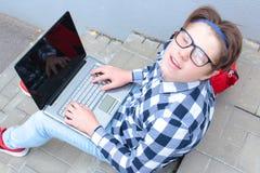 Den pojketonåringskolpojken eller studenten sitter på trappan och att arbeta i datoren, bärande exponeringsglas, i en skjorta och Arkivbilder