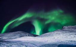 Den polara arktiska för norrskenhimmel för nordliga ljus stjärnan i Norge Svalbard i berg för Longyearbyen stadsmåne Arkivfoto