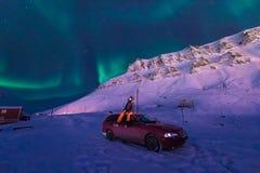 Den polara arktiska stjärnan för himmel för norrsken för nordliga ljus för man i Norge Svalbard i berg för Longyearbyen stadsmåne Arkivbilder