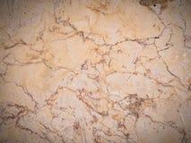 Den polerade stenväggen i beiga tonar med karaktärsteckning Royaltyfri Foto