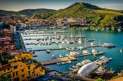 Den Porto Ercole byn och hamnen i ett hav sk?ller E royaltyfria foton