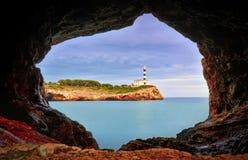 Den Portocolom fyren, stenar grottan, det lugna blåa havet, mallorca, Spanien arkivbilder