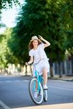 Den positiva attraktiva flickan i vita blått för tappning för klänning- och sugrörhattridningen cyklar på sommardag Arkivbild