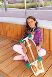 Den positiva flickan rymmer skateboarden, medan sitta Royaltyfria Bilder