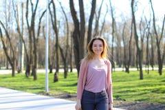 Den positiva flickan som in går, parkerar och att le fotografering för bildbyråer