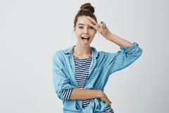 Den positiva flickan visar henne sinnesrörelser Inomhus skott av den attraktiva spensliga caucasian kvinnliga studenten som ut kl arkivfoto