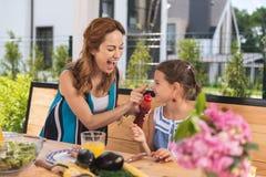 Den positiva gladlynta kvinnan som sätter ketchup på hennes döttrar, nose royaltyfri fotografi
