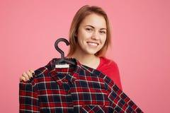 Den positiva gladlynta unga kvinnan annonserar den trendiga rutiga skjortan på hängare, föreslår att köpa den med lågpris, föresl arkivfoto