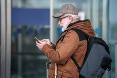 Den positiva gråhåriga mannen är den hållande smartphonen royaltyfria bilder