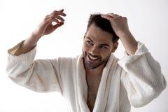 Den positiva gulliga skäggiga grabben gör frisyren royaltyfria foton