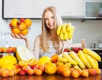 Den positiva kvinnan med bananer och annan bär frukt Royaltyfri Fotografi