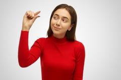 Den positiva kvinnan med den stilfulla frisyren, visar något som mycket är mycket liten eller som är liten och att vara i bra lyn royaltyfri bild