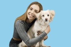 Den positiva kvinnlign med glat uttryck och hennes hund som tillfredsställs efter, går utomhus-, har bra förhållanden royaltyfri foto
