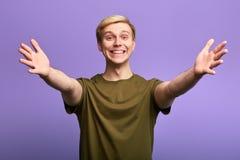 Den positiva lyckliga stiliga mannen som välkomnar folk med hans armar, öppnade royaltyfria bilder